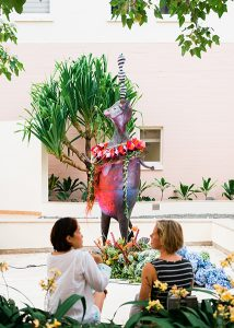 "View of the bronze sculpture ""Mr. Chickenpants"" adorned with lei. In the background there is a hala tree. In the foreground, two people sit and talk next to a border of yellow flowers."